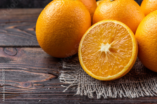Oranges on dark wooden background. - 253674777