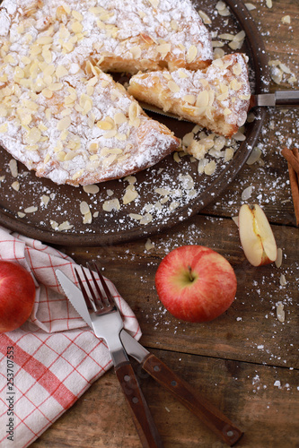Sweet homemade apple pie on a plate with fresh apples and cinnamon sticks on a rustic wooden table