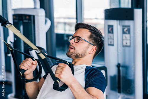 Close-up of sportsman in eyeglasses working out on TRX. - 253708317