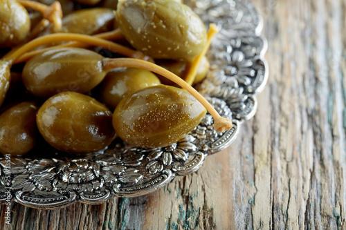 Leinwanddruck Bild Pickled caper berries in metal dish .