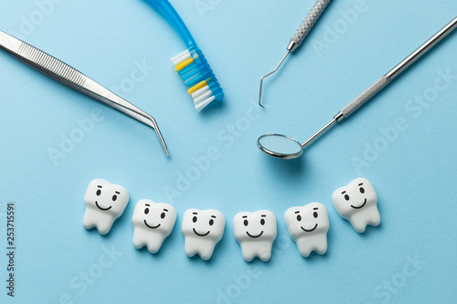 Healthy white teeth are smiling on blue background and dentist tools mirror, hook.