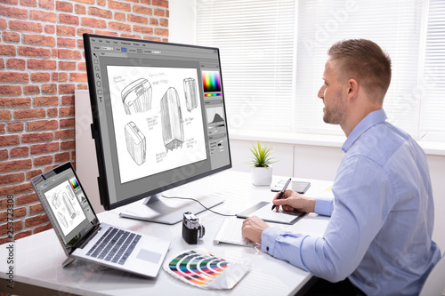 Designer Drawing Suitcase On Computer Using Graphic Tablet