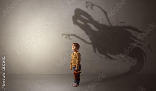 Leinwanddruck Bild Scary ghost shadow in a dark empty room with a cute blond child