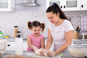 Mother And Daughter Kneading Dough On Kitchen Counter