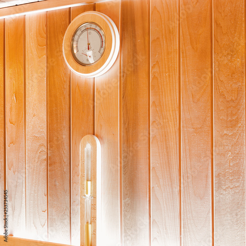 Leinwanddruck Bild Round thermometer and hourglass on the wall of traditional sauna