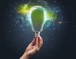 Leinwandbild Motiv Hand holding light bulb on dark background. New business idea concept