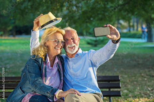 Leinwandbild Motiv Senior couple taking a selfie photo with smart phone in a park