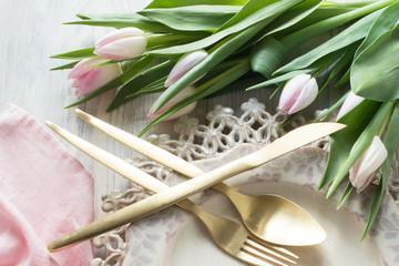 antike Teller, Tulpen und Besteck in rosa
