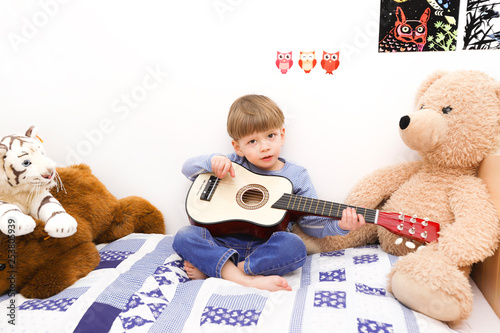 Ein kleiner Junge spielt auf einer Gitarre - 253805939