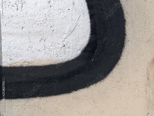 Fragment of a concrete wall with black paint