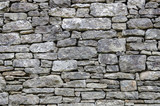 Stone rock wall with beautiful pattern for background.  Texture and design in this stonework aged structure.