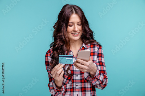 young girl isolated over blue background using mobile phone holding credit card.