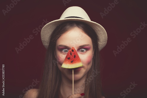 Leinwandbild Motiv Attractive Lovely girl with pink make up, wearing jeans, hat and top, posing at red studio background, holding slice watermelon and eat it , emotionally look, close up portrait