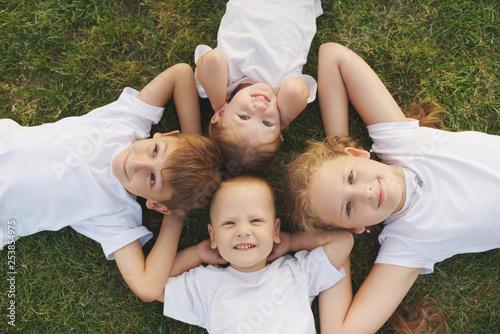 happy chiuldren lying on green grass