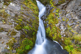 A small waterfall in the mountains between two moss-covered cliffs