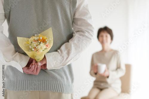 妻への花束を持つシニア男性の後姿