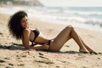 Arabic woman with beautiful body in bikini lying on the beach sand