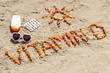 Medical pills, inscription vitamin D and accessories for sunbathing on sand at beach, concept of prevention of vitamin D deficiency