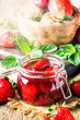 Leinwanddruck Bild - Strawberry confiture with whole berries, vintage wooden kitchen table background, summer preservation of jam and cooking, selective focus
