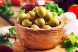 Salted Spanish green olives in wooden bowl and appetizers, rustic style, selective focus