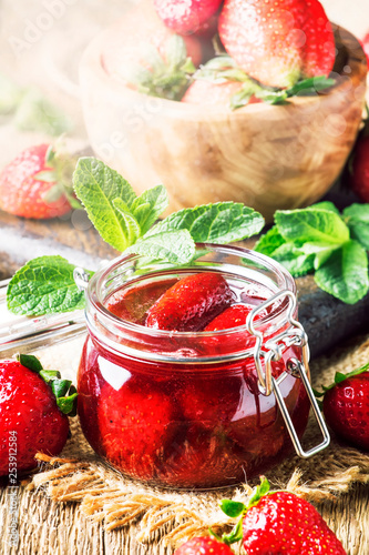 Strawberry confiture with whole berries, vintage wooden kitchen table background, summer preservation of jam and cooking, selective focus - 253912584