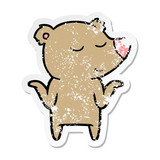 distressed sticker of a happy cartoon bear shrugging shoulders