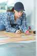 young woman measuring plank of wood - 253938943