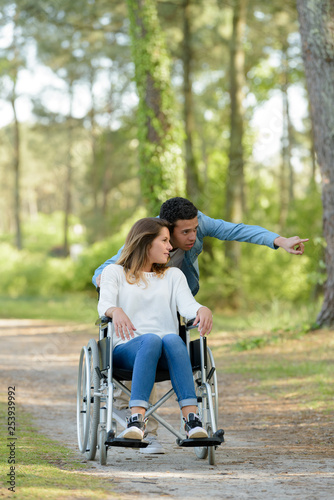 young man pushing girlfriend in wheelchair in the countryside