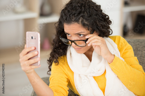 young lady loweing eyeglasses to view smartphone