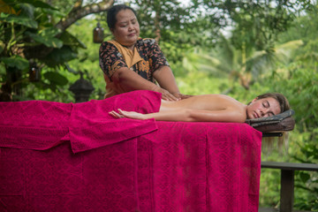 masseuse does massage to pretty young woman lying on massage table outdoors