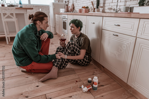 Husband holding hand of wife having problems with alcohol