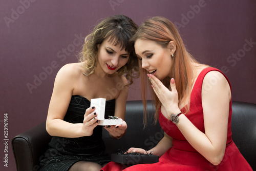 Gold jewelry in the hands of a beautiful girl. Two women are looking at a large, thick gold jewelry chain. © ALEXEY