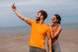 Young sports couple taking selfie on the beach