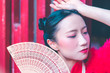 Young chinese woman with Fan on red background for chinese new year concept