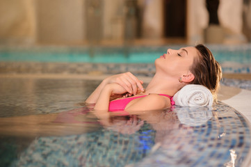 lateral view of a beautiful woman wearing swimsuits relaxing in jacuzzi