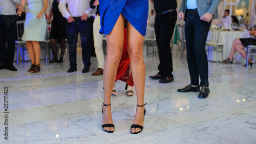mata magnetyczna close up photo of woman legs in stylish high hell shoes on floor dancing at a wedding party