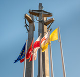 Monument to the fallen workers of shipyard at Solidarnosc Square in Gdansk with flags in front.