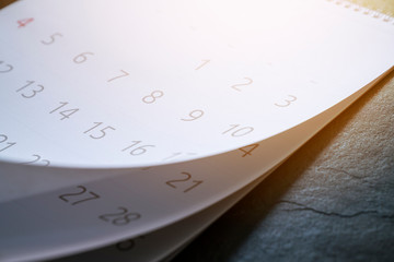 close up of calendar on the table with sunlight, planning for business meeting or travel planning concept