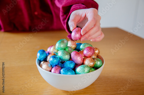 female hands try to take Easter eggs in plate