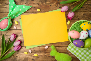 Easter holiday background with paper note, easter eggs in basket and tulip flowers on wooden table.
