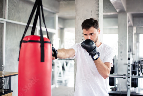 Portrait handsome man practicing boxing on a punching bag at gym