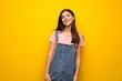 Teenager girl over yellow wall laughing looking to the front