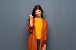 Leinwanddruck Bild - Teenager girl with coat over grey wall with angry gesture