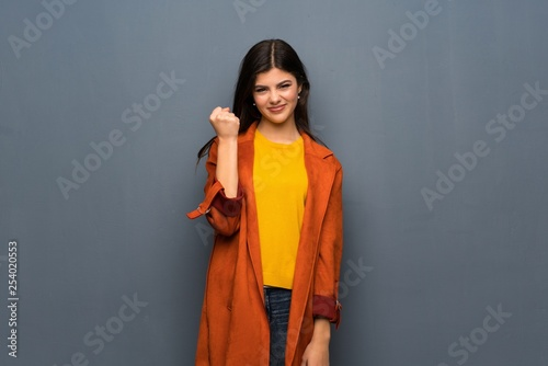 Leinwanddruck Bild Teenager girl with coat over grey wall with angry gesture