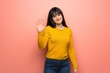 Woman with yellow sweater over pink wall saluting with hand with happy expression