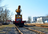 Railway crane on the platform, moving along the railway track. Special construction train for maintenance of railway, rail, sleepers