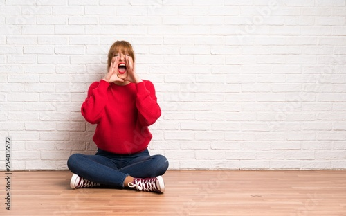 Leinwanddruck Bild Redhead woman siting on the floor shouting and announcing something