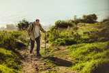 Man trekking up a hill using hiking poles