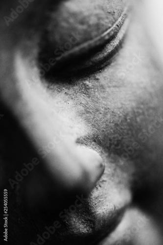 Black and white photo of a Buddha face close up shot. Buddhist religion concept idea - 254055559