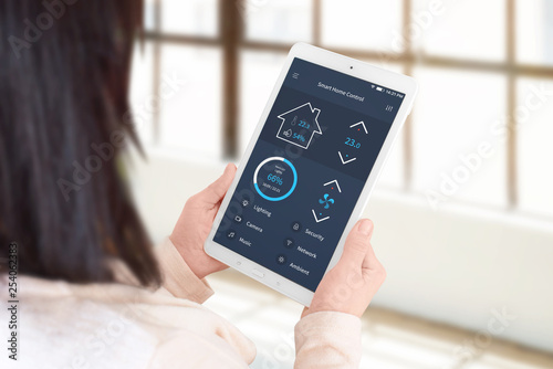 Woman use smart home control app to set the temperature and lighting. Living room, home management concept.